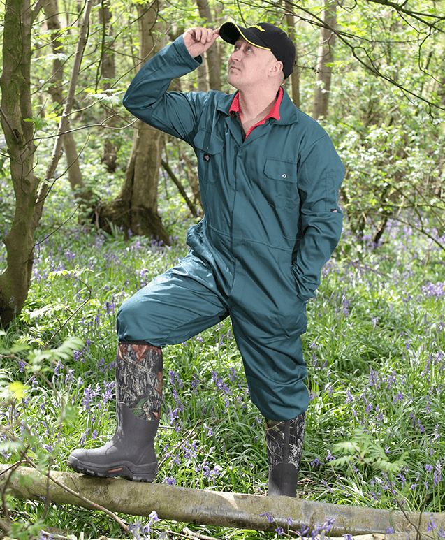 A man looking over woodland in farming wellies and country clothing