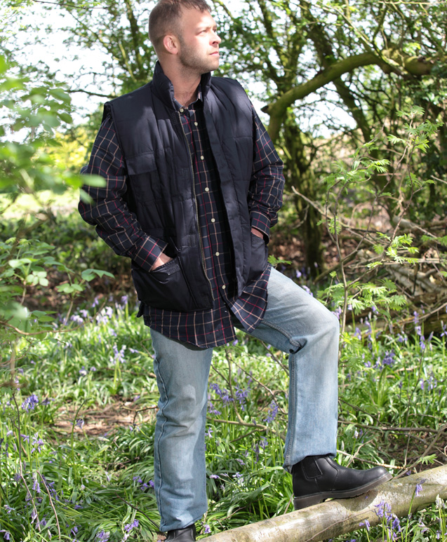 A man standing on a log wearing long country boots